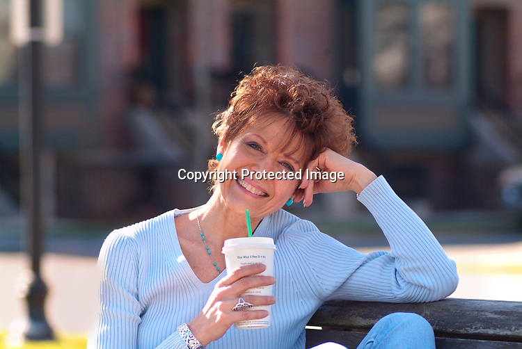 Redheaded woman enjoying coffee and sun in park