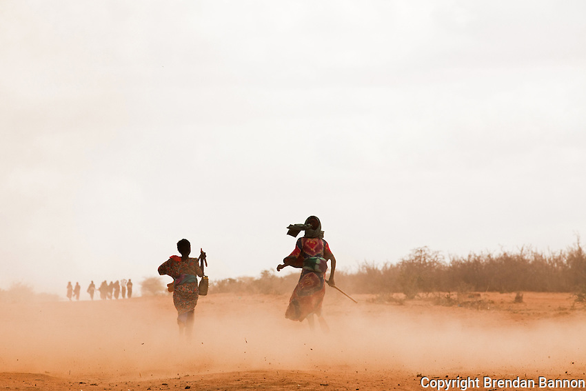 Two Somali refugee girls run through a dust storm on the outskirts of Ifo settlement near Dadaab, Kenya They are part of a recent exodus from Somalia due to continued civil war and  the consequences of drought and famine.