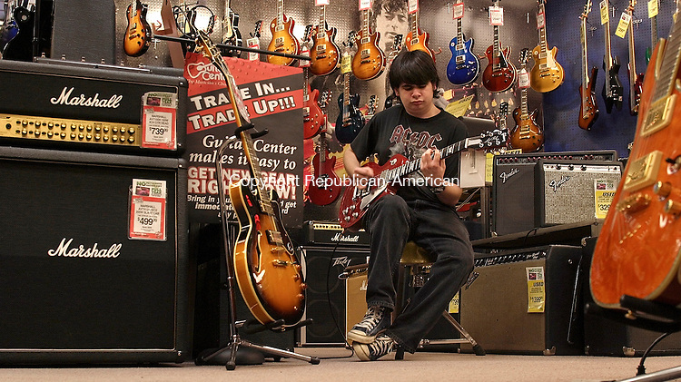 WATERBURY, CT - 23 March 2004 - 032304TH09 - Devin Ezk, 14 of Pomfret, checks out one of the huge selections of guitars at the Guitar Center in Manchester Tuesday night.  TODD HOUGAS PHOT