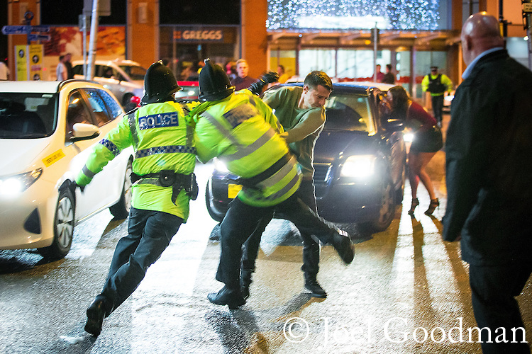 © Joel Goodman - 07973 332324 . 01/01/2016 . Manchester , UK . Police attempt to detain a man who has been fighting with another . Revellers in Manchester on a New Year night out at the clubs around the city centre's Printworks venue . Photo credit : Joel Goodman
