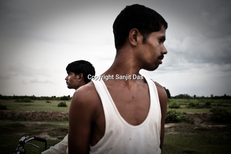 Shatrughan Lal (right) and Deepak Kumar (left) are seen next to their barren farmlands in village Rajagaon of block Machreta in Uttar Pradesh, India. The 4 month annual rainfall is crucial to summer sown crops as 60% of the farmlands are rainfed. North India experienced scanty rainfall in late june to july. Till August, rain in India has been 26% below 5 yea average. Late rains moist the fields but it is not enough for rice, sugarcane, oilseeds and pulses. Late rains also damage the alternate crops that need less water.
