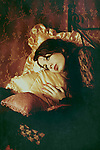 A woman in a victorian outfit lying on the golden pillows in a dreamy pose