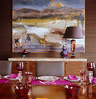 Across the dining table a large landscape painting is displayed above a contemporary marble-topped sideboard