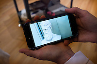 """Conservator Regina Gaudette shows an image on her phone of the damaged nose on a marble bust of abolitionist John Brown in the Tisch Family Gallery at the Tufts University Art Gallery at Tufts University in Medford, Massachusetts, on Thurs., Oct. 6, 2016. The bust was sculpted by Edward Augustus Brackett and had been improperly stored for decades with a broken nose and eyebrow. The conservators, from Rika Smith McNally and Associates, found a plaster cast made from the original at the Boston Athenæum and had a 3D modeler image the broken section of the original and the cast. They then used 3D printing technology to use to create a plaster nose replacement that would fit perfectly on the broken marble bust. They then used gouache paint to match the replacement pieces to the original marble.  The bust is part of an exhibition at the gallery entitled """"Mortal Things: Portraits Look Back and Forth."""""""