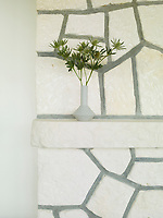 In the living area, original features like the limestone fireplace have been retained. A small vase with an arrangement of sea holly stands on the mantelpiece.