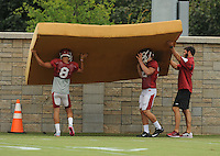 NWA Democrat-Gazette/ANDY SHUPE<br /> Arkansas punter Blake Johnson (8) and an unidentified player carry a large piece of foam Tuesday, Aug. 18, 2015, during practice at the university's practice field in Fayetteville.