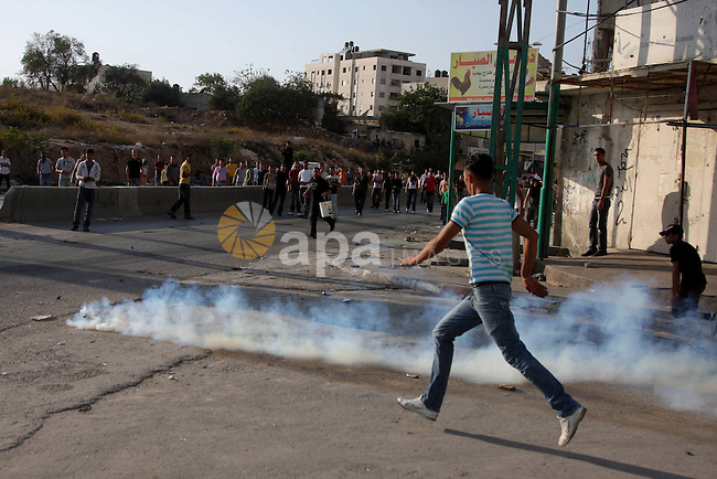 Palestinian youth runs for cover during clashes at the Kalandia checkpoint near the West Bank city of Ramallah October 9, 2009. Palestinian leaders on Thursday called for a one-day general strike and warned of more street protests over Jerusalem, where clashes at the flashpoint al-Aqsa mosque two weeks ago cranked up tensions in the disputed city. Israel is playing down Palestinian warnings that its security tactics risk a new Palestinian uprising. Photo by Issam Rimawi