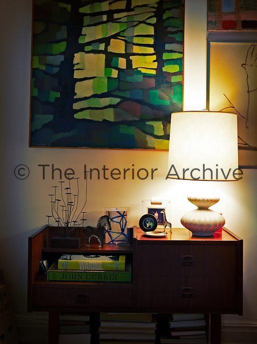 A lit lamp and ornaments stand on a retro style bedside table. An artwork of green and yellow hues hangs on the wall.