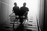 Switzerland. Canton Bern. Bienne. Expo 02. Migros area. Sideshow: Strangers in paradise. Two men side by side, like a couple, seated in a maxi shopping cart on their way to the sky. © 2002 Didier Ruef