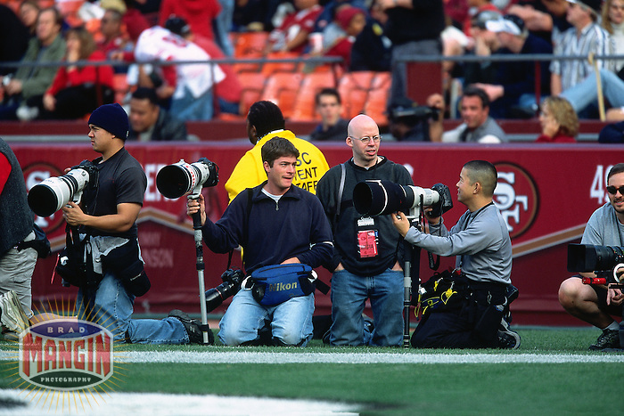 SAN FRANCISCO, CA - Sports photographers Jeff Chiu, Jed Jacobsohn, Grover Sanschagrin and Rod Mar shoot from the sidelines during a football game between the Seattle Seahoawks and San Francisco 49ers at Candlestick Park in San Francisco, California on December 1, 2002. (Photo by Brad Mangin)