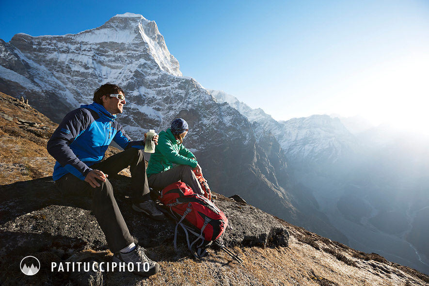 Two hikers stopped and relaxing in the sun while hiking the 5200 viewpoint above Tangnac (Thangnak), a popular day trip while acclimating on the Mera Peak Trail. The distant mountain is Kyashar (Tangste) 6800 meters. Nepal Himalaya.