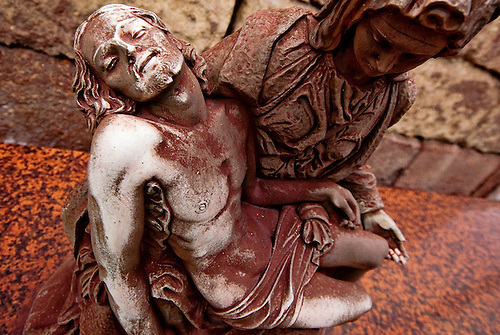 Taranto Italy 2010<br /> A detail of a statue representing a Piet&aacute; completely covered with red dust of iron  situated in the public cemetery of Tamburi quarter in Taranto.