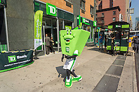 A costumed actor welcomes visitors to the TD Bank sponsored festivities at the grand opening of a new branch in the Chelsea neighborhood of New York on Friday, September 18, 2015. TD Bank has seen growth recently through expansion of its retail banking network and the acquisition of other banks. (© Richard B. Levine)