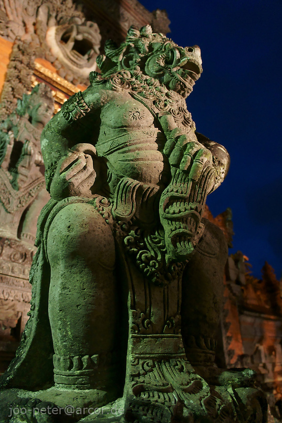 night scene with vulcano stone sculpture of a protective spirit  in front of temple in Peliatan Banjar Pande, next to Ubud, Bali, archipelago Indonesia