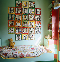 Illustrated squares depicting the alphabet are mounted on the wall above a child's bed covered in a colourful patchwork quilt