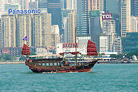 Rusty Chinese Junks, barges and the ubiquitous green and white Star Ferry boats crisscross the famous Victoria Harbor in the shadows of Hong Kong Island's towering skyscrapers..
