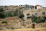 A Palestinian woman walks past a house belonging to a Palestinian family on May 17, 2013 in front of houses in the Mitzpe Lachish Israeli settlement outpost (background) in the West Bank village of Beit Awwa. Israeli settlement watchdog Peace Now said on May 16, 2013 that the government wants to give retroactive approval to four West Bank settlement outposts it had previously pledged to at least partially demolish. Givat Assaf, Givat Haroeh, Maaleh Rehavam and Mitzpe Lachish outposts are among six listed in a 2005 government report as deserving immediate eviction and later ordered shut by a court order. Photo by Mamoun Wazwaz