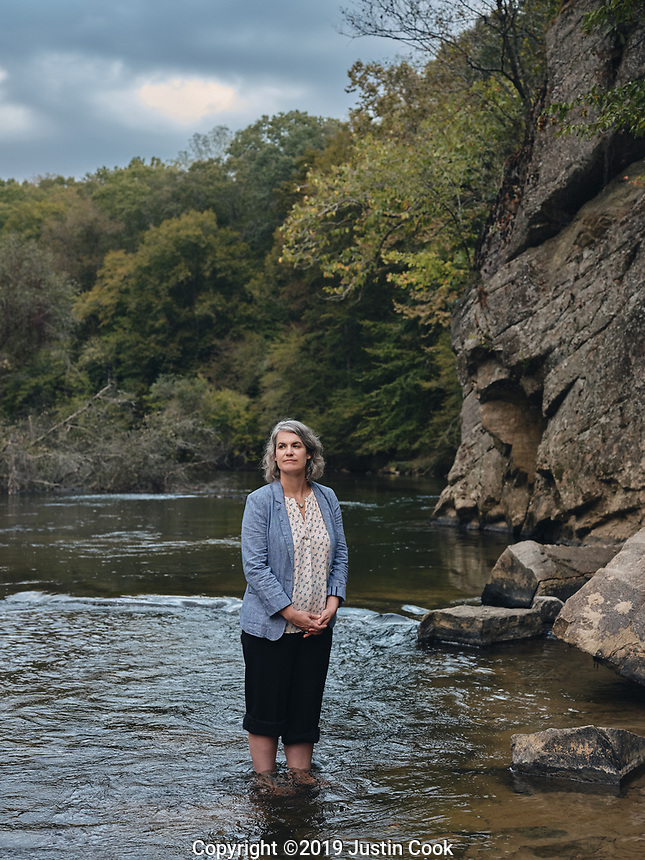 Portrait of Caroline Armijo at Moratock State Park on the Dan River in Danbury, North Carolina, Saturday, October 12, 2019 . In 2014, a leak from a Duke Energy site left coal ash coating 70 miles of the Dan River on the North Carolina-Virginia border. Caroline Armijo is environmental advocate and artist who now lives in Greensboro, North Carolina, but grew up in Stokes County where the coal ash spill took place. Her work incorporates her concern for environmental issues threatening her home community – coal ash and fracking. She advocates with Residents for Coal Ash Clean Up, which supports the Belews Creek Community and Alliance of Carolinians Together (ACT) against Coal Ash. (Justin Cook)