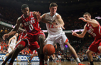 Virginia guard Joe Harris (12) reaches for the loose ball with North Carolina State guard Rodney Purvis (0) and North Carolina State forward Scott Wood (15) during the game Saturday in Charlottesville, VA. Virginia defeated NC State 58-55.