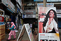 A muslim woman pass electronic shops with advertising poster showing woman with camera. Srinagar, Kashmir,India. © Fredrik Naumann/Felix Features