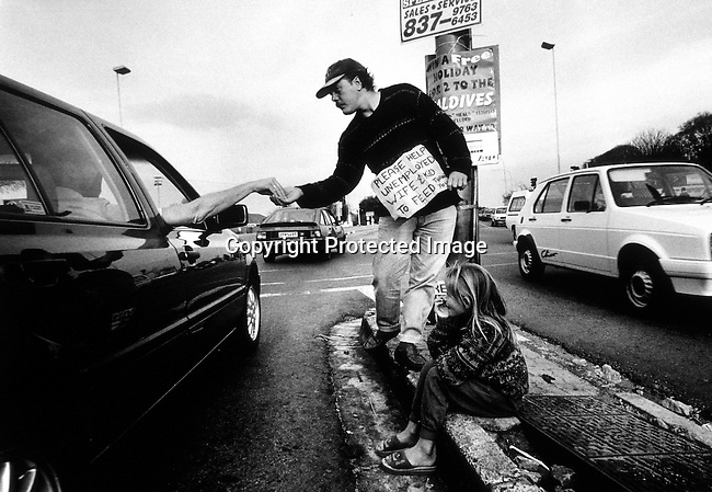 disipov00073.Social Issues. Poverty. Wilhelm Fourie, an unemployed man with daughter Bianca on September 22, 1998 begging at a busy intersection in Cresta, Johannesburg South Africa. Mr Fourie lost his job and have difficulties to find a new one due to affirmative action policies in the new South Africa. More and more white people are seen unemployed and begging since the first democratic election in 1994 in the country..©Per-Anders Pettersson/iAfrika Photos