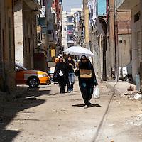 White umbrella over women walking in black burqa in Suez alley.