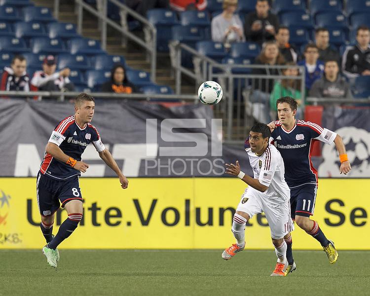 Real Salt Lake midfielder Javier Morales (11) works to clear ball as New England Revolution defender Chris Tierney (8) and New England Revolution midfielder Kelyn Rowe (11) close.