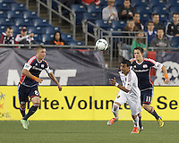 Real Salt Lake midfielder Javier Morales (11) works to clear ball as New England Revolution defender Chris Tierney (8) and New England Revolution midfielder Kelyn Rowe (11) close.