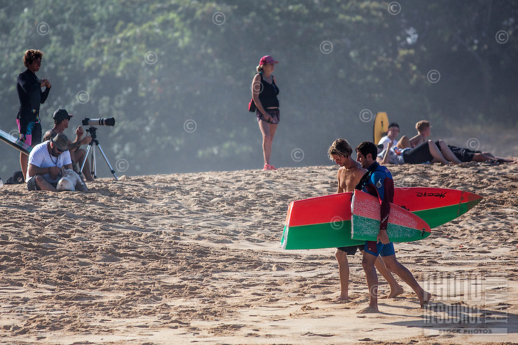 A friend walks with a fellow surfer carrying broken surfboard, Waimea Bay, North Shore, O'ahu.