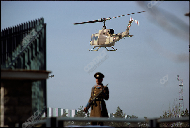 A Huey helicopter carries the shah and the empress to the Imperial Pavilion at Mehrabad Airport for their flight into exile. Tehran, January 16, 1979