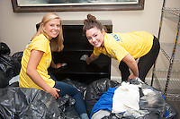 Emma Sherr,'20, and Gianna Gebhard,'20, clean shelving units as they help out at the Seamen's Church Institute in Newport as part of Salve Regina's Exploration Day of Service.