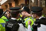 A police sergeant is treated by medics after sustaining a cut to his face from missiles thrown by the demonstrators outside Conservative Party Headquarters on Millbank. 10/11/2010