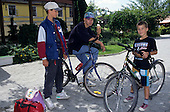 Hungary. Three boys; one eating ice cream; two bicycles.