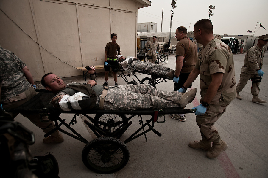"""Two American soldiers with minor wounds from an IED that damaged their armored vehicle are taken into the military hospital at Kandahar Airfield. Scenes from the medical evacuations of wounded Americans, Canadians, and Afghan civilians and soldiers being flown by Charlie Co. 6th Battalion 101st Aviation Regiment of the 101st Airborne Division. Charlie Co. - which flies under the call-sign """"Shadow Dustoff"""" - flies into rush the wounded to medical care out of bases scattered across Oruzgan, Kandahar, and Helmand Provinces in the Afghan south. These images were taken of missions flown out of Kandahar Airfield in Kandahar Province and Camp Dwyer in Helmand Province."""