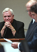 Monsignor William V. Sullivan, pastor of St. Ann's Catholic Church in Ashland, Virginia, looks at a note he took during a call about the sniper shootings during his testimony in the trial of sniper suspect John Allen Muhammad in courtroom 10 at the Virginia Beach Circuit Court in Virginia Beach, Virginia on October 30, 2003. <br /> Prince William County (Virginia) prosecutor Paul Ebert, second from right, and defense attorney Jonathan Shapiro, right, look over evidence. <br /> Credit: Adrin Snider - Pool via CNP