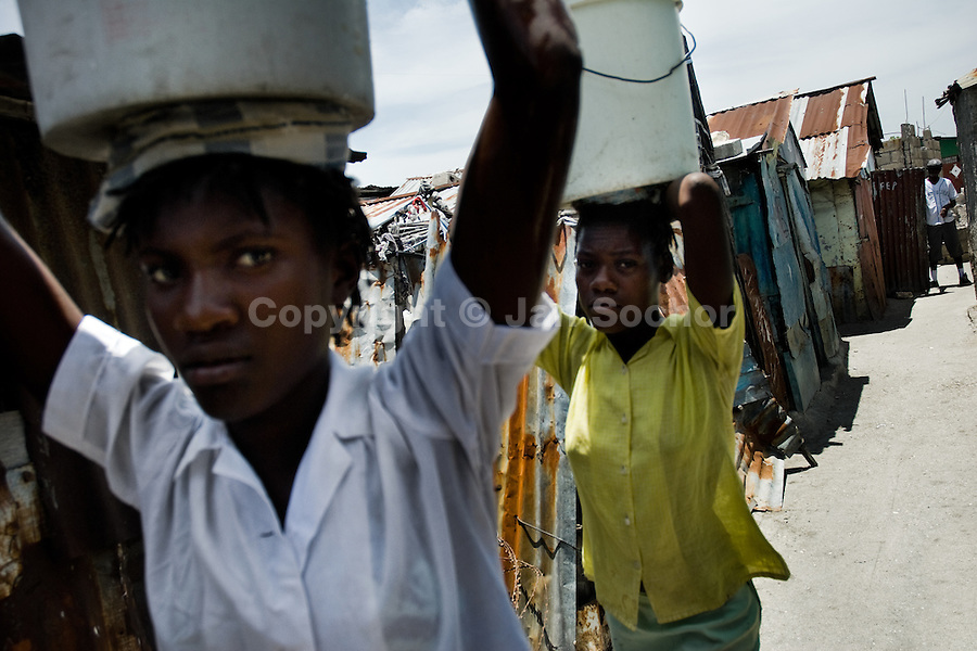 Haitian women carries buckets of drinking water in the slum of Cité Soleil, Port-au-Prince, Haiti, 16 July 2008. Cité Soleil is considered one of the worst slums in the Americas, most of its 300.000 residents live in extreme poverty. Children and single mothers predominate in the population. Social and living conditions in the slum are a human tragedy. There is no running water, no sewers and no electricity. Public services virtually do not exist - there are no stores, no hospitals or schools, no urban infrastructure. In spite of this fact, a rent must be payed even in all shacks made from rusty metal sheets. Infectious diseases are widely spread as garbage disposal does not exist in Cité Soleil. Violence is common, armed gangs operate throughout the slum.
