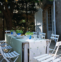 A rustic table surrounded by white painted garden chairs has been draped in lengths of fabric to create an outdoor dining area