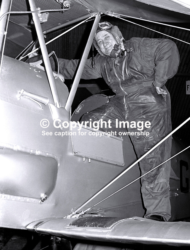 Tubby Dash, 73 years,  former chief flying instructor, Ulster Flying Club, Newtownards, N Ireland, in early aviator style kit, goggles and helmet, getting into the cockpit of a Tiger Moth. 1974082104555TD2..<br />