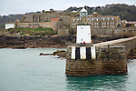 Lighthouse at harbour entrance with Castle Cornet behind, St Peter Port, Guernsey, Channel Islands, UK