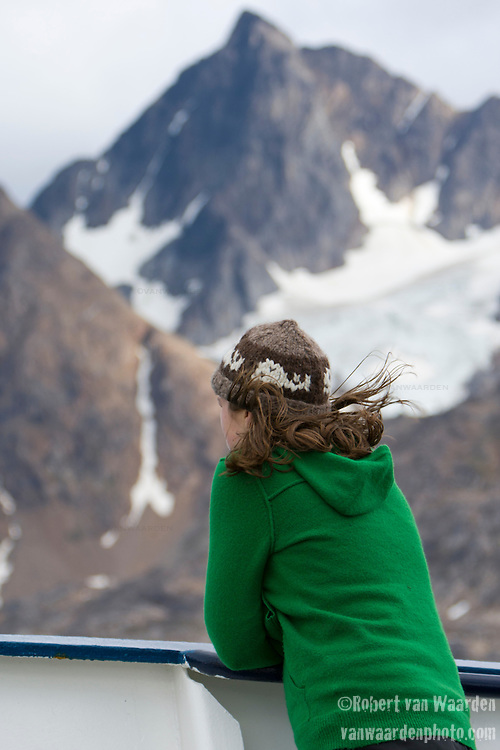 The wind blows a young woman's hair during an Arctic expedition in Greenland. In the background, the mountains of Greenland's east coast near Ammassalik.