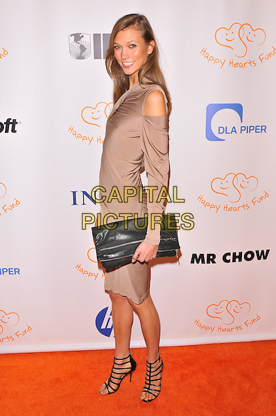 Karlie Kloss.2011 Happy Hearts Fund: Land Of Dreams, Haiti, New York City, NY, USA..November 5th, 2011.full length black strapy sandals clutch bag beige dress cut out away shoulder side .CAP/ADM/CS.©Christopher Smith/AdMedia/Capital Pictures.