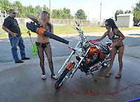 NWA Democrat-Gazette/MICHAEL WOODS • @NWAMICHAELW<br /> Kim Whisler (right) and Michelle Stroud both from Kansas City, work on drying off a motorcycle for Ed Stovall of Cave Springs (left) Friday September 25, 2015 at the bikini bike wash at the Washington County Fairgrounds in Fayetteville. The bikini bike wash will be open at the Fairgrounds through out the bike rally.  The 16th annual Bikes, Blues and BBQ Motorcycle Rally runs through Saturday on Dickson Street, Baum Stadium and the Washington County Fairgrounds in Fayetteville and all day Saturday at Arvest Ballpark in Springdale.