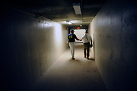 Designated hitter Tim Tebow (15) of the Columbia Fireflies walks down the tunnel toward the clubhouse with a security guard after a game against the Lexington Legends on Thursday, June 8, 2017, at Spirit Communications Park in Columbia, South Carolina. Columbia won, 8-0. (Tom Priddy/Four Seam Images)