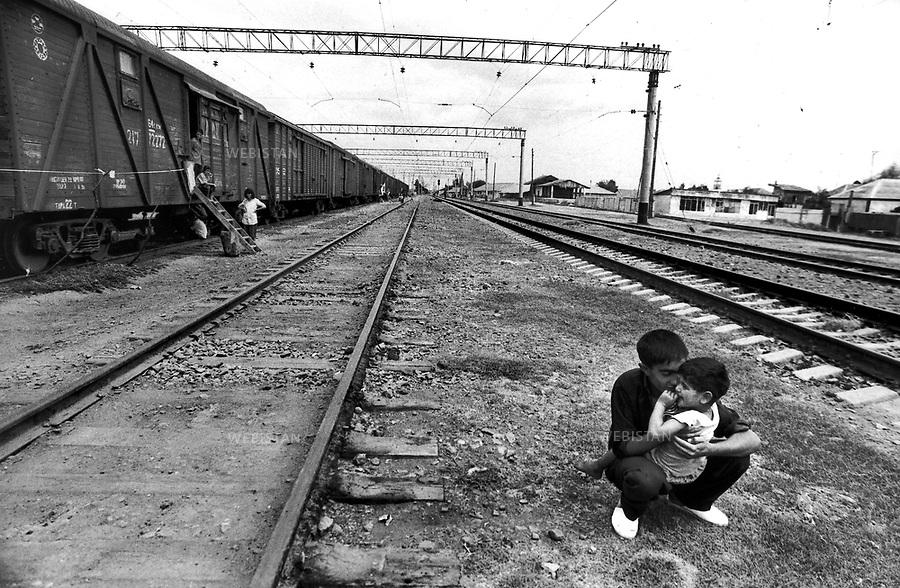 1997..Azerbaijan. Near Baku. In a disused station, an Azerbaijani refugee family who fled the Nagorno-Karabakh conflict, live in the wagons of an abandoned train, on the outskirts of Baku...Azerbaïdjan. Près de Bakou. Dans une gare désaffectée, une famille de réfugiés azerbaïdjanais qui ont fui le conflit du Haut-Karabakh, vivent dans les wagons d'un train abandonné, à la périphérie de Bakou... ..