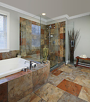 Contemporary earthtone marble tiled bath with whirlpool tub and oversized glass walled corner shower.