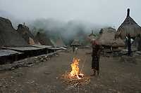 elder villager at fire on village court in foggy dawn time, village Bena, Ngada people, Flores, Indonesia
