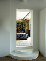 View through the contemporary doorway of the master bedroom where a large tapestry hangs on the stone wall