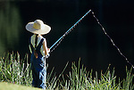 Young girl (7 years old) wearing straw hat fishing alone,  along lake in rural Snohomish County, Lake Pleasant, Bothell, Washington State USA