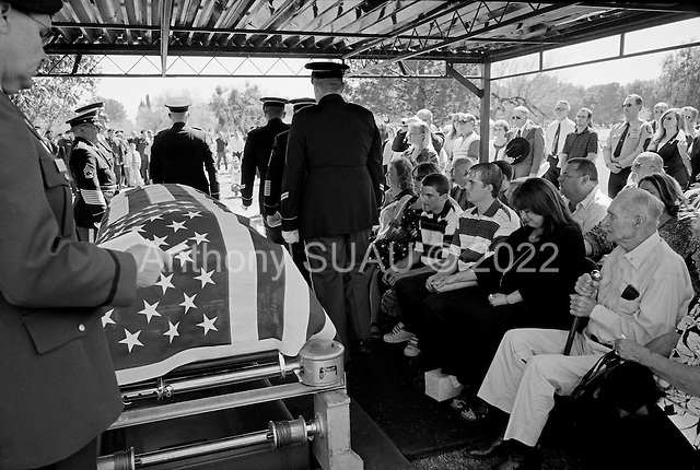 Tucson, Arizona.USA.March 16, 2007..At the Evergreen Cemetery Lori Kasson, the widow of Staff Sgt. Darrel D. Kasson, 43, of Florence, Arizona with her three children (to her right) Jeremy (19), Dale (15), daughter Lisa Varnes (22), and (to her left) grandfather Leo at the funeral services for her husband. He died March 4 in Tikrit, Iraq, of wounds suffered when an improvised explosive device detonated near his vehicle at Bayji, Iraq. He was assigned to the 259th Security Forces Company, Phoenix.