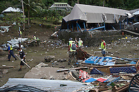 Police officers and volunteers search through debris for missing persons at the Boomerang Resort along the coast that bore the full force of the tsunami. More than 170 people died when a tsunami triggered by an 8.3 magnitude earthquake hit Samoa and neighbouring Pacific islands on 29/09/2009. Samoa (formerly known as Western Samoa)..